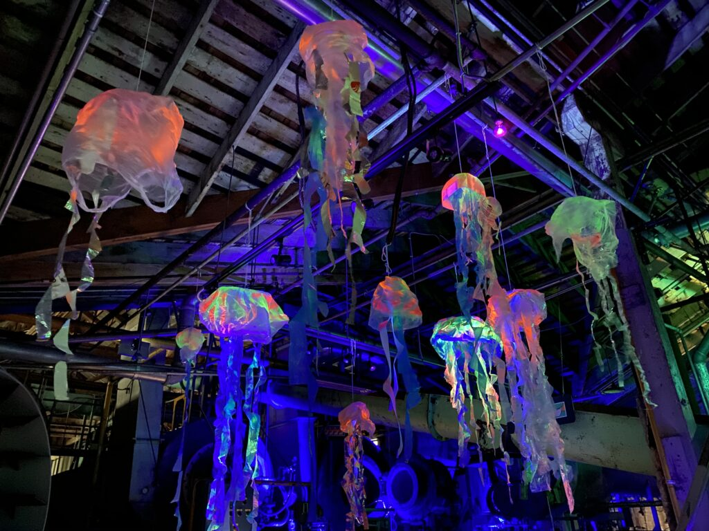 Glow in the dark plastic jellyfish hanging from ceiling